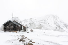 Winter in the Alps. Lonely building on the top of a snowy hill Stock Photo