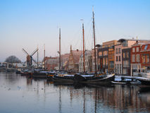 Winter in Amsterdam. View of winter Amsterdam with old historical building, canal, boats and windmill stock photography