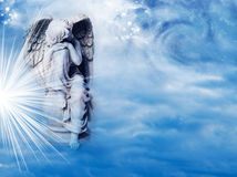 Winter angel. An angel statue over mystical sky with divine light and stars Royalty Free Stock Photo