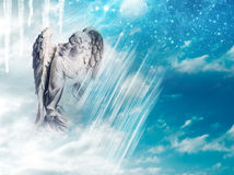 Winter angel. An angel statue over mystical sky with divine light and stars stock image