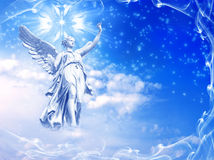 Winter angel. A statue of angel over winter sky with snow flakes with copy space royalty free stock image