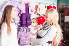 Winter apparel shop. Mother with baby visit the apparel shop with  winter wear Stock Image