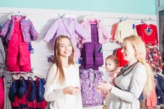 Winter apparel shop. Mother with baby visit the apparel shop with  winter wear Royalty Free Stock Photos