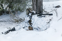 Winter arctic mountains sniper. Winter arctic mountains warfare. Action in cold conditions. Sniper with weapons in forest somewhere above the Arctic Circle Stock Image