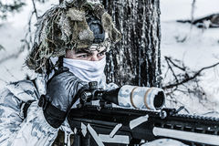 Winter arctic mountains sniper. Winter arctic mountains warfare. Action in cold conditions. Sniper with weapons in forest somewhere above the Arctic Circle Stock Images