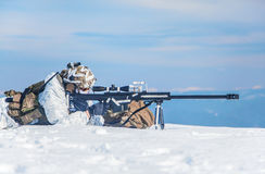 Winter arctic mountains warfare. Army soldier with Sniper rifle in action in the Arctic. He lies in the snow desert, suffering from extreme cold, but waiting as Royalty Free Stock Photography