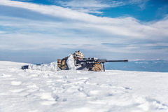 Winter arctic mountains warfare. Army soldier with Sniper rifle in action in the Arctic. He lies in the snow desert, suffering from extreme cold, but waiting as Stock Image