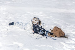 Winter arctic mountains warfare. Army soldier with Sniper rifle in action in the Arctic. He lies in the snow desert, suffering from extreme cold, but waiting as Royalty Free Stock Images