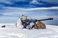 Winter arctic mountains warfare. Army soldier with Sniper rifle in action in the Arctic. He lies in the snow desert, suffering from extreme cold, but waiting as Stock Photography