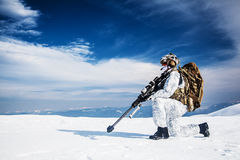 Winter arctic mountains warfare. Army soldier with Sniper rifle in action in the Arctic. He wears chest rig, backpack, suffers from extreme cold, strong wind Stock Image