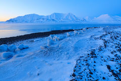 Winter Arctic. White snowy mountain, blue glacier Svalbard, Norway. Ice in ocean. Iceberg twilight in North pole. Beautiful landsc Stock Images