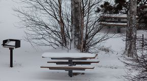Empty snow covered picnic tables and grill in the park royalty free stock image