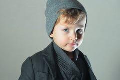 Winter-Art Little Boy Stattliches Kind Kinder in der erwachsenen Kleidung schutzkappe Blaue Augen Stockbild