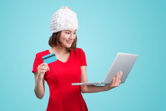 Winter asian woman holding laptop and credit card against blue v. Ignette royalty free stock image