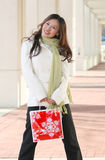 Winter: Asian Woman with Holiday Shopping Bag. Attractive Asian Woman in White winter Coat with Red Holiday Shopping Bag on a Street, suitable for a variety of Royalty Free Stock Photos