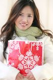Winter: Asian Woman with Holiday Shopping Bag. Attractive Asian Woman in White winter Coat with Red Holiday Shopping Bag on a Street, suitable for a variety of Stock Photo