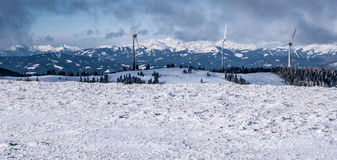 Winter austrian alps panorama with wind turbines and snow covered peaks Stock Photo