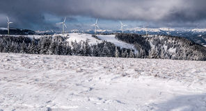 Winter austrian alps with wind turbines and peaks Royalty Free Stock Images