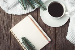 Winter and autumn composition. Top view of vintage notebook with fir tree and pencil, decorated with cup of coffee Stock Photos