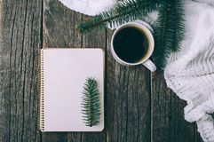 Winter and autumn composition. Top view of vintage notebook with fir tree and pencil, decorated with cup of coffee Stock Image