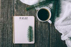 Winter and autumn composition. Top view of vintage notebook with fir tree and pencil, decorated with cup of coffee Royalty Free Stock Images