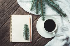 Winter and autumn composition. Top view of vintage notebook with fir tree and pencil, decorated with cup of coffee Royalty Free Stock Photos