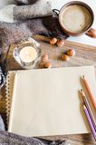Vintage notebook with pencils, candle and coffee. Winter and autumn composition. Vintage notebook with pencils, candle and cup of coffee and warm plaid. Top view Royalty Free Stock Photography
