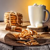 Winter autumn still life  homemade recipe honey ginger oatmeal cookie and bagel, cocoa cup coffee with marshmallow o. N wooden table kitchen Jute, burlap Rustic Stock Photos