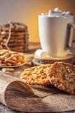 Winter autumn still life  homemade recipe honey ginger oatmeal cookie and bagel, cocoa cup coffee with marshmallow o. N wooden table kitchen Jute, burlap Rustic Royalty Free Stock Photography