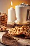 Winter autumn still life  homemade recipe honey ginger oatmeal cookie and bagel, cocoa cup coffee with marshmallow o. N wooden table kitchen Jute, burlap Rustic Royalty Free Stock Photos