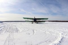 Winter aviation. There is a green biplane on the runway. stock image
