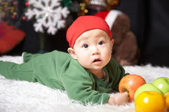 Winter baby. Baby holding fruits at christmas eve Stock Photos