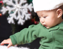 Winter baby. Baby boy in winter and a big snowflace in background Royalty Free Stock Images