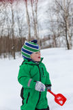 Winter baby activity. Winter baby with shovel happiness in snow Royalty Free Stock Images