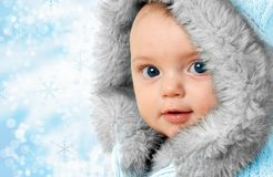 Winter baby. Beautiful baby girl on a snow flake background wearing a winter fur coat Stock Photography