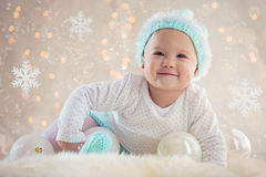 Winter Baby Smiling With Christmas ornaments stock images