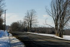 Winter Back Roads in Vermont. Blue sky and trees on this back road in Vermont.  The sun is shining through the trees from the east Stock Image