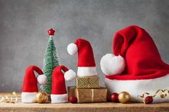 Winter background with Christmas gift or present boxes, Santa hats and holiday decorations. Greeting card. stock photography