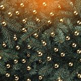 Winter background of fir branches. Adorned with gold baubles. Christmas card. Top view. Xmas congratulations royalty free stock photo