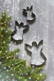 Winter background with fir branches, garland and cookie cutters on a gray concrete background. Greeting card. royalty free stock photography