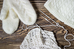 Winter background. Knitting, crochet. White mittens and hat. Stock Photo