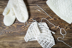 Winter background. Knitting, crochet. White mittens and hat. Royalty Free Stock Images