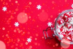 Winter background -red and white candies in glass jar, on red ba Stock Images