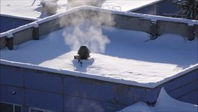 Winter background the roof of a modern building covered with snow. Smoke coming from the chimney, sunny frosty day, snowflakes glisten in the sun stock footage
