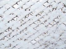 Winter background. Snow on the iron grid. Stock Photos