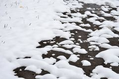 Winter background. The snow is melting and looking through the ground.  stock photography