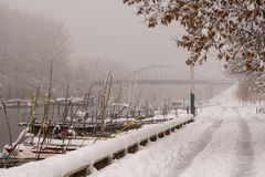 Winter background with snow on the riverside with boats. Fogy winter day on the river with frost and snow.  royalty free stock photos