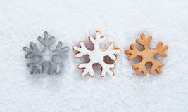 Winter background with snowflakes. Winter background with three different snowflake biscuits in row on a bed of fresh snow for use in a winter theme or for your Stock Photo