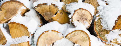 Winter background  texture pattern with stacked dry chopped firewood logs covered with snow Royalty Free Stock Photography