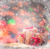 Winter background wrapped gifts wooden trunk snowing Stock Photography